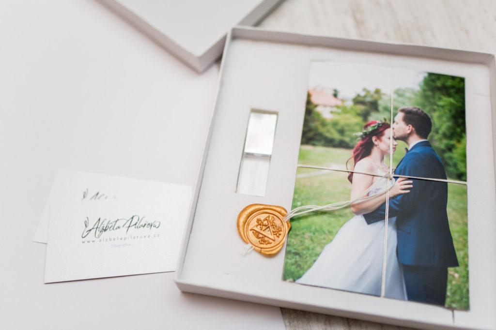 Dárkově zabalené fotografií s pečetí připravené na předání novomanželům