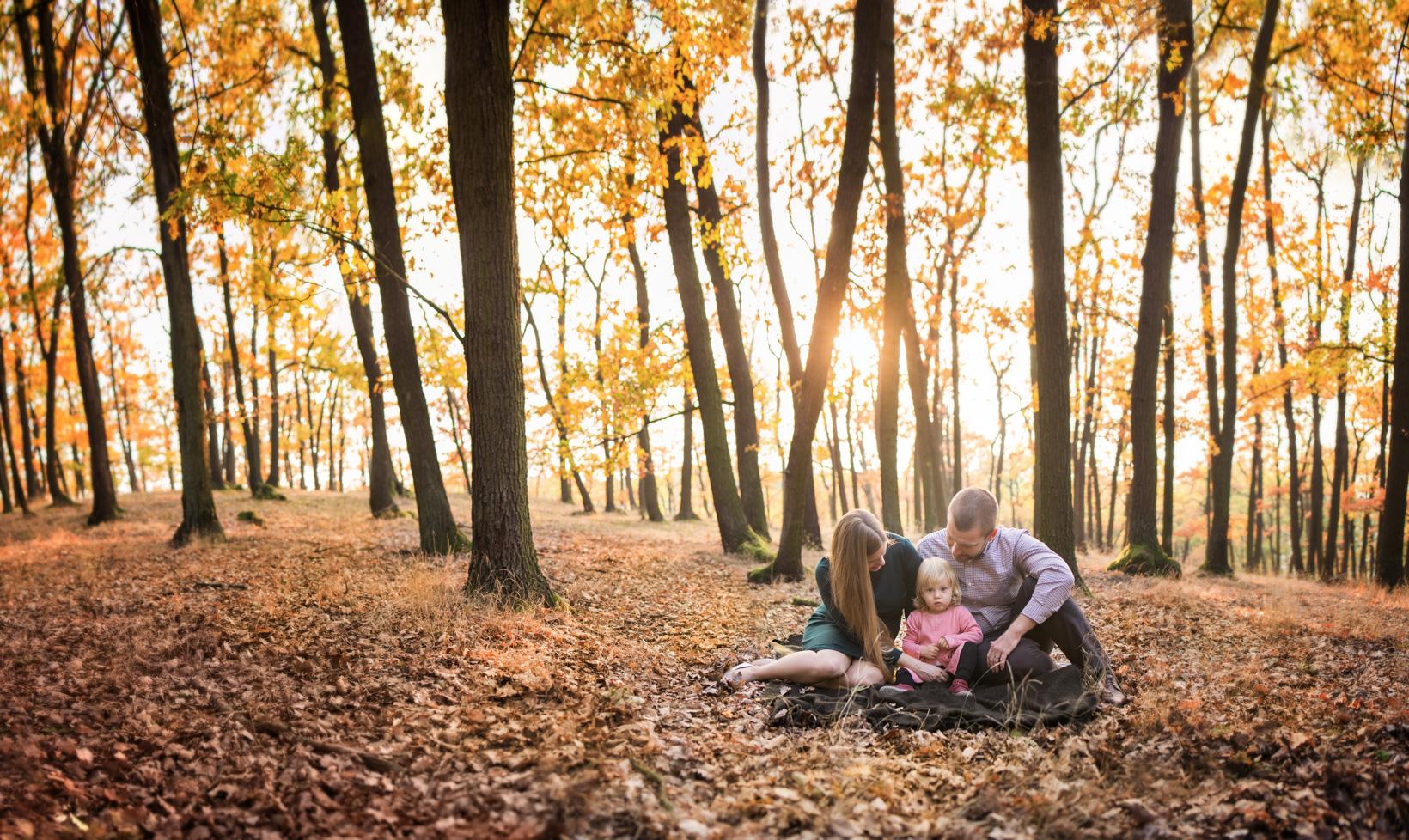 Malá rodina v podzimním lese se zapadajícím sluncem