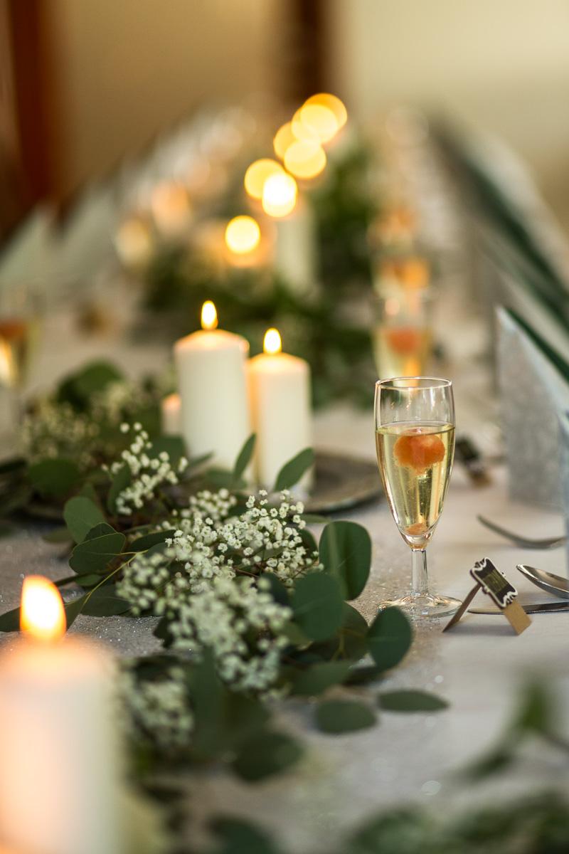 Svatební stůl vyzdobený svíčkami, eukalyptem a nevěstiným závojem