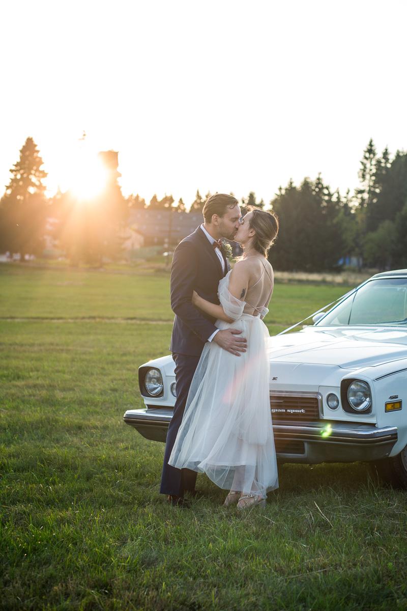 Portrét novomanželů se zapadajícím sluncem a vintage autem